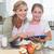 happy mother and daughter preparing cake together stock photo © wavebreak_media