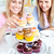 Positive young women eating cakes in the kitchen at home stock photo © wavebreak_media