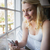 pretty blonde sitting by the window sending a text stock photo © wavebreak_media