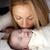 loiro · little · girl · beijando · mãe · cama - foto stock © zdenkam