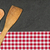 wooden spoon on a slate plate with a red checkered tablecloth stock photo © zerbor