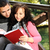 young couple girl and boy sitting in park and reading a book stock photo © zurijeta
