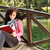 young beautiful girl student sitting on wooden bridge over the bridge in nature and reading a book stock photo © zurijeta